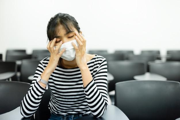 A jovem mulher asiática com máscara profilática vestindo da higiene tem sintomas doentes, dor de cabeça que senta-se na sala de reunião.