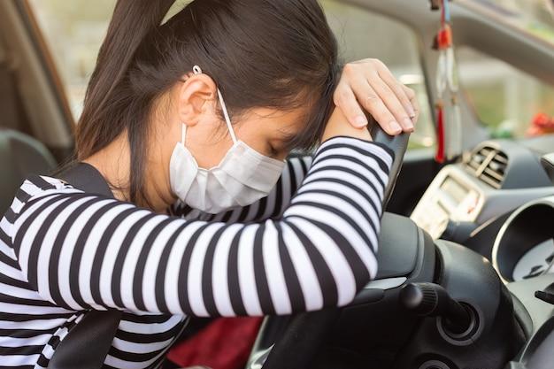 A jovem mulher asiática com máscara profilática vestindo da higiene tem sintomas doentes, dorme na cara do carro no volante.
