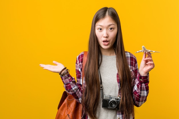 A jovem mulher asiática segurando um ícone de avião impressionou segurando o espaço em branco na palma da mão.