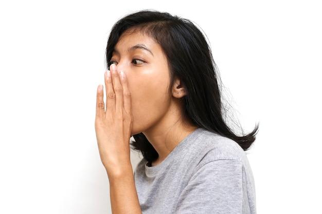 A jovem mulher asiática sussurrando um segredo por trás da mão no espaço em branco