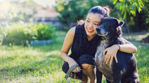 A jovem mulher asiática toma o cão para andar e jogar junto no jardim em casa.