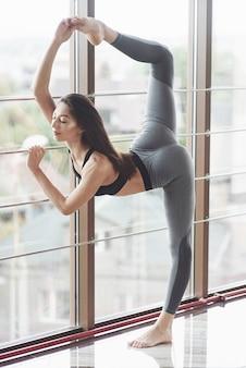 A jovem mulher atraente ioga praticando o treino está em roupas esportivas.