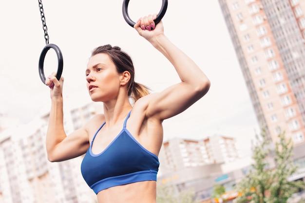 A jovem mulher atrativa do ajuste na menina do desgaste do esporte levanta nos anéis na área do exercício da rua.