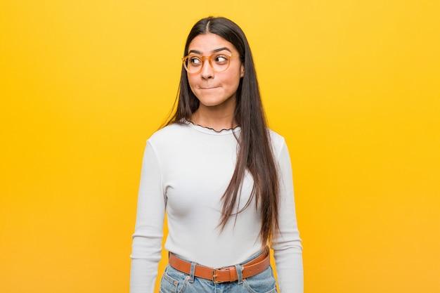 A jovem mulher bonita árabe contra uma parede amarela confusa, sente-se duvidosa e insegura.