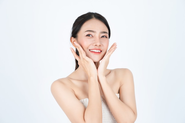 A jovem mulher bonita asiática na camiseta branca, tem uma pele saudável e brilhante.