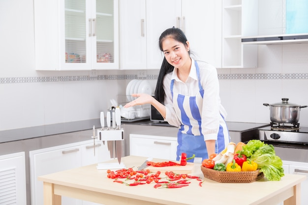 A jovem mulher bonita asiática no cozinheiro está misturando a massa.