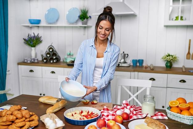 A jovem mulher bonita derrama a massa para a torta de maçã na cozinha branca.