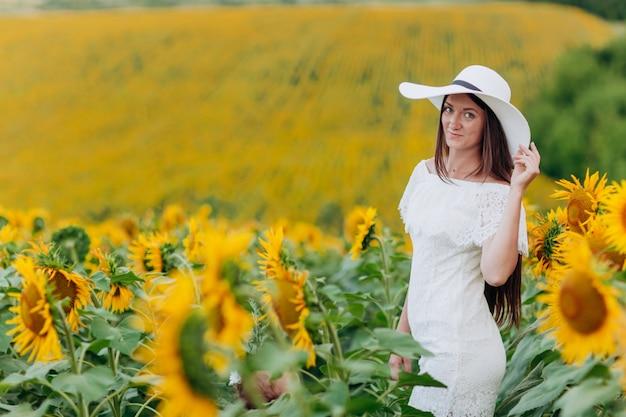 A jovem mulher bonita em girassóis de florescência coloca no verão. menina elegante com cabelos longos, vestido e chapéu branco. férias de verâo