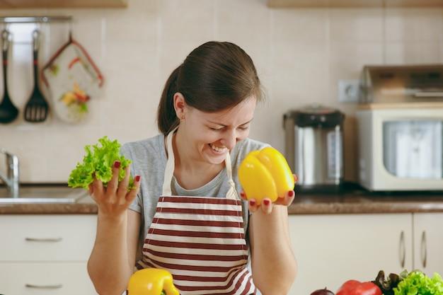 A jovem mulher bonita em um avental com folha de alface e pimentão amarelo rindo na cozinha. conceito de dieta. estilo de vida saudável. cozinhando em casa. preparar comida.