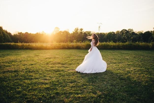 A jovem mulher bonita em um vestido de casamento branco e as botas pretas no por do sol são fotografadas.