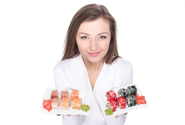 A jovem mulher bonita está guardando uma placa com sushi.