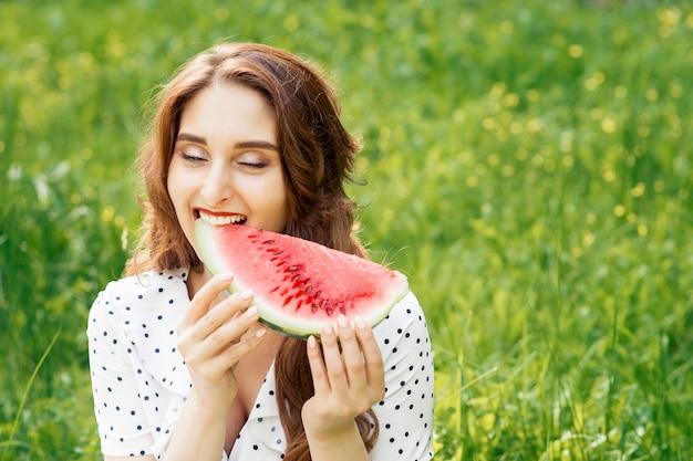 A jovem mulher bonita está mordendo a fatia de melancia no fundo da grama.
