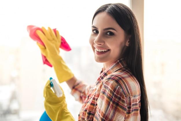 A jovem mulher bonita está sorrindo ao limpar a janela.