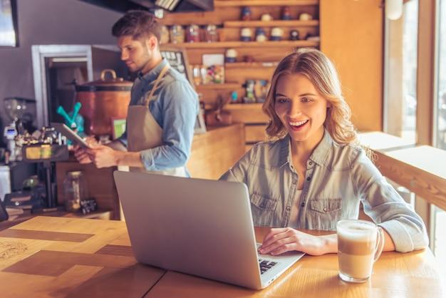A jovem mulher bonita está sorrindo ao trabalhar com portátil.