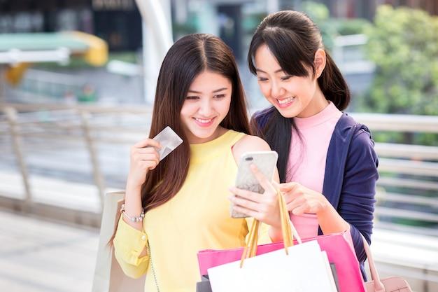A jovem mulher bonita feliz aprecia comprar com smartphone, cartão de crédito a comprar, e o saco de compras e o telefone celular.