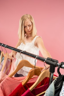 A jovem mulher bonita infeliz olhando vestidos e experimentá-lo ao escolher na loja