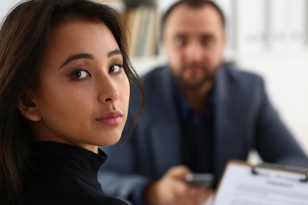 A jovem mulher bonita senta-se na cadeira na mesa no escritório no gabinete de seu chefe segurar a pasta nos braços
