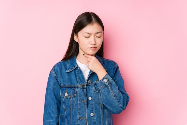 A jovem mulher chinesa que levanta em uma parede cor-de-rosa isolada sofre a dor na garganta devido a um vírus ou uma infecção.