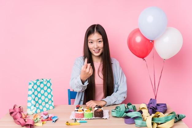 A jovem mulher chinesa que organiza um aniversário isolou apontar com o dedo em você como se convidando se aproximar.