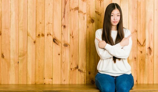 A jovem mulher chinesa que senta-se em um lugar de madeira aponta lateralmente, está tentando escolher entre duas opções.