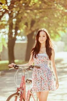 A jovem mulher com bicicleta no parque