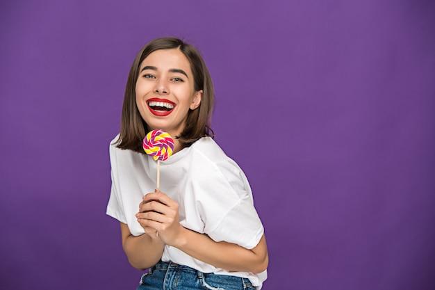 A jovem mulher com pirulito colorido