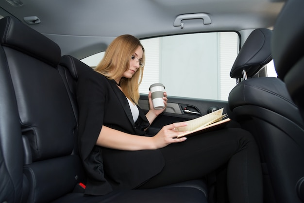 A jovem mulher com um caderno e uma xícara de café está sentando-se no carro no banco traseiro.