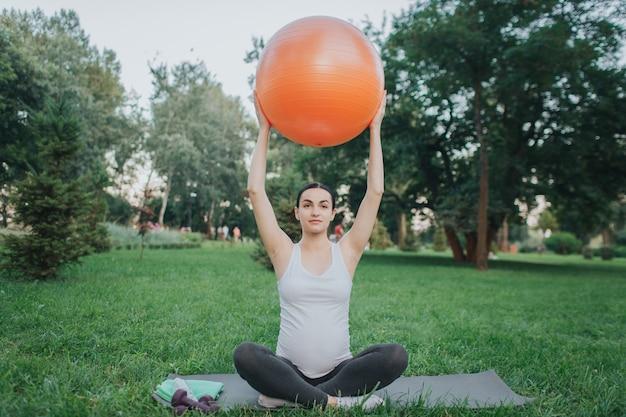 A jovem mulher concentrada senta-se na pose dos lótus no companheiro de ioga no parque. ela segura a bola laranja fitness com as mãos.