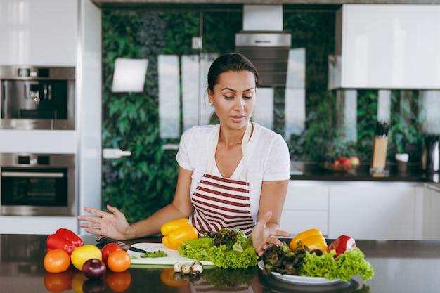 A jovem mulher confusa e pensativa de avental decide o que cozinhar na cozinha