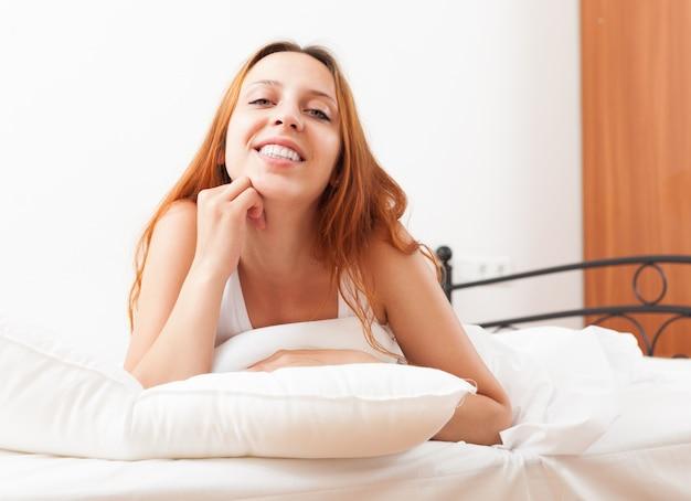 A jovem mulher de cabelos compridos acorda na cama
