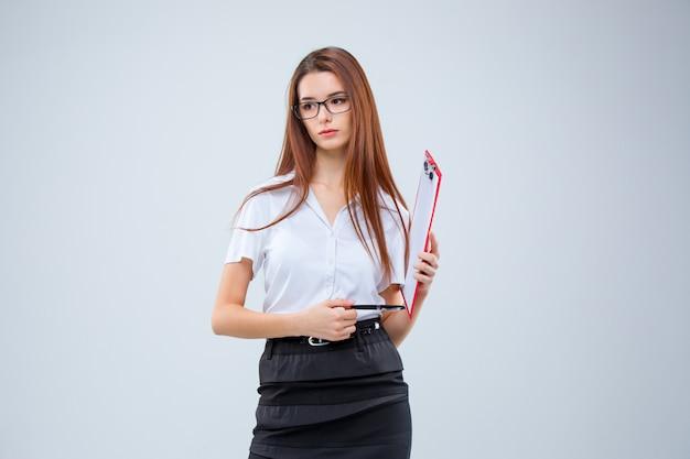A jovem mulher de negócios com caneta e tablet para anotações em cinza