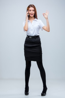 A jovem mulher de negócios com o telefone em um cinza
