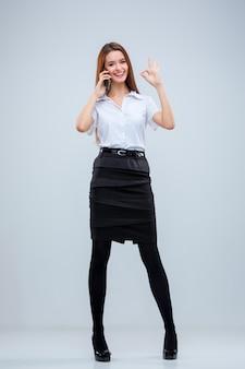 A jovem mulher de negócios com o telefone em um fundo cinza