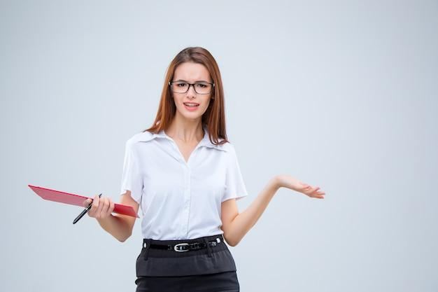 A jovem mulher de negócios de óculos com caneta e tablet para anotações em um cinza
