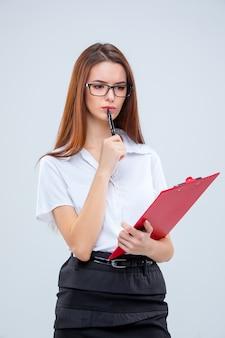 A jovem mulher de negócios de óculos com caneta e tablet para anotações em um fundo cinza