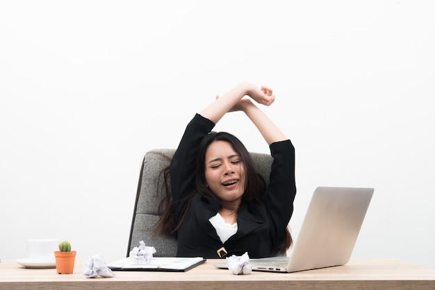 A jovem mulher de negócios parece estressante e cansada sentada no local de trabalho com laptop na mesa isolada no fundo branco
