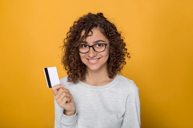 A jovem mulher de sorriso com vidros da raça misturada guarda um cartão de crédito. fêmea afro preta feliz no estúdio em um fundo amarelo.