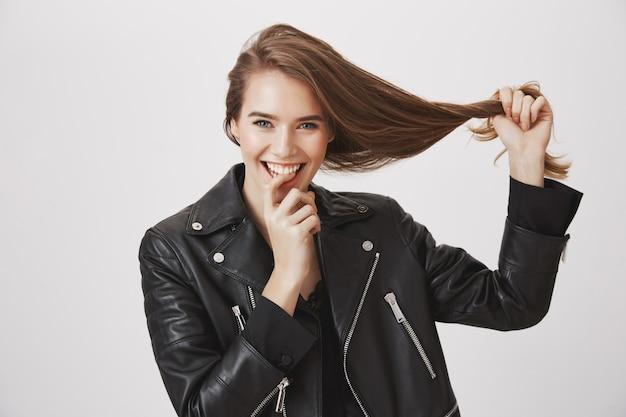 A jovem mulher de sorriso puxa o cabelo, conceito de produtos do haircare