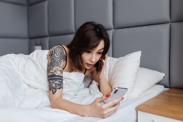 A jovem mulher de sorriso segura o smartphone que encontra-se acordado na cama na manhã