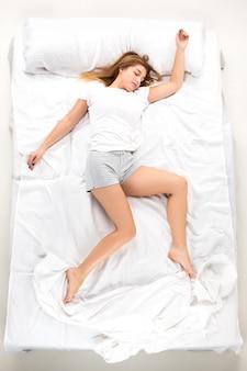 A jovem mulher deitada em uma cama