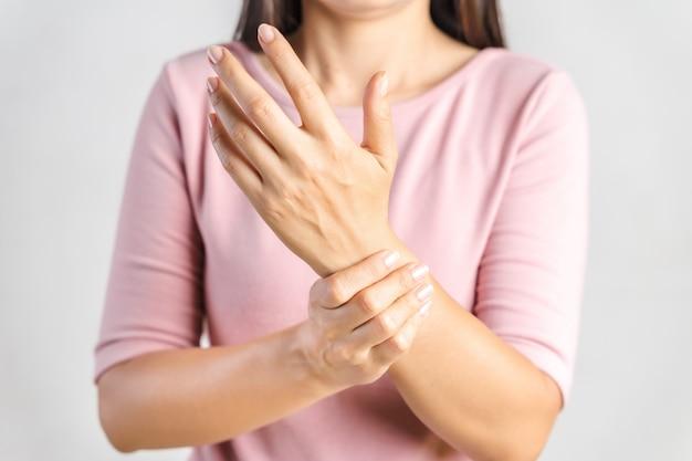 A jovem mulher do close up prende seu pulso no branco. lesão na mão, sentindo dor. cuidados de saúde e conceito médico.