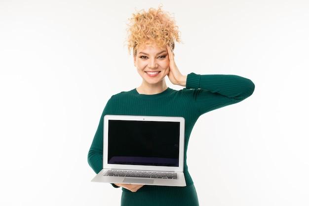 A jovem mulher do sorriso prende o caderno com maquete com a tela para a frente no branco