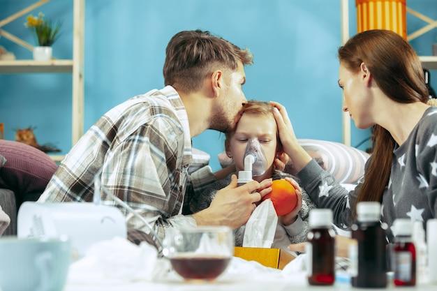 A jovem mulher e o homem com a filha doente em casa. tratamento em casa. lutando com uma doença. saúde médica. a ilusão familiar. o inverno, gripe, saúde, dor, paternidade, conceito de relacionamento