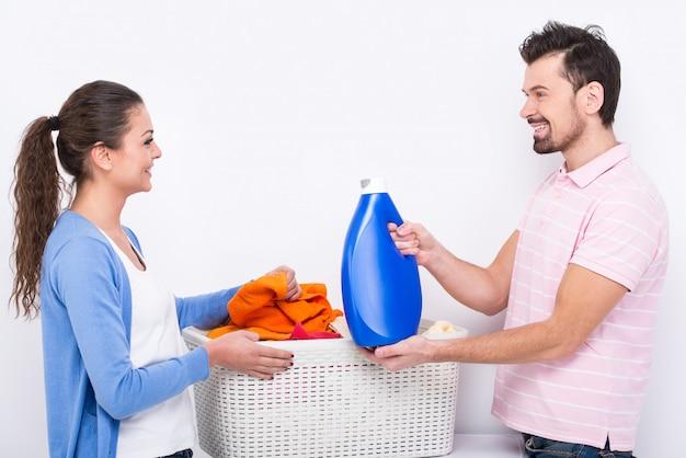 A jovem mulher e o homem estão fazendo a lavanderia em casa.