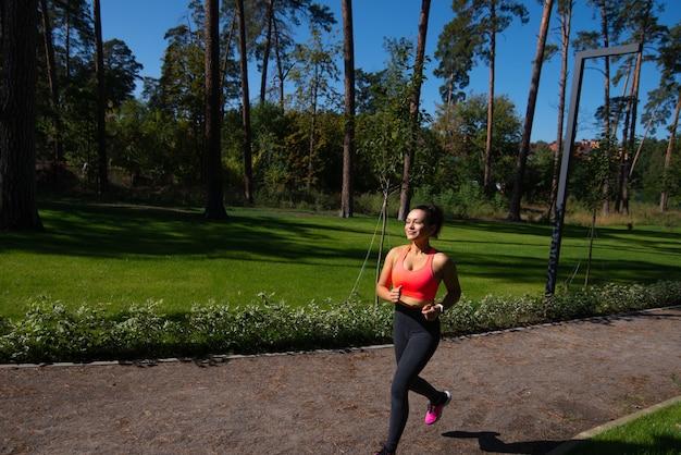 A jovem mulher em roupas esportivas corre no parque num contexto de grama verde. esportes ao ar livre.