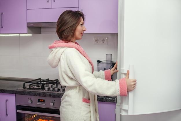 A jovem mulher em um roupão de banho abre a geladeira