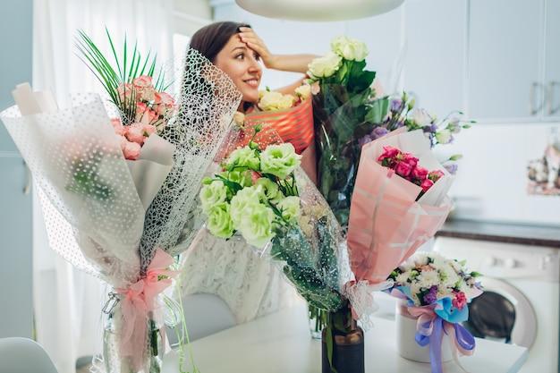 A jovem mulher encontrou muitos buquês de flores na cozinha. garota animada feliz sorrindo