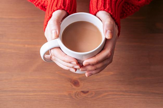 A jovem mulher entrega guardar uma caneca de café quente sobre uma mesa de madeira. copie o espaço. vista aérea. hora de relaxar.