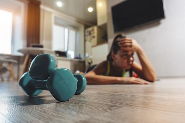 A jovem mulher está cansada durante o exercício com halteres em casa