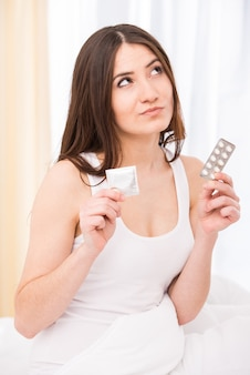 A jovem mulher está escolhendo seu caminho - preservativo ou comprimidos.